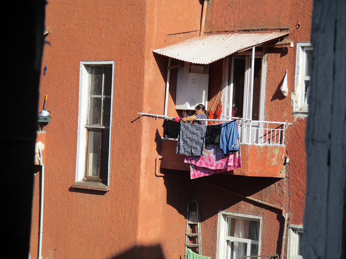 13-15 Years: Woman Hanging Clothes On The Balcony